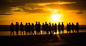 GROUP LINE AT SUNSET ON PLAYA GUIONES
